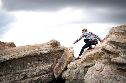 Fille qui tente de faire le saut entre deux gros rochers