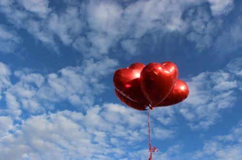 Paquet de ballons rouges en forme de coeur dans le ciel